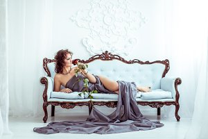 Beautifu woman lying on couch and holding red rose