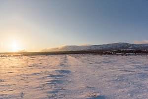Winter road to the forest. Sunset landscape. Snow covered field.