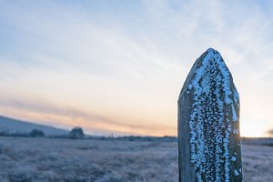 Close up of a wooden pole in winter landscape sunset