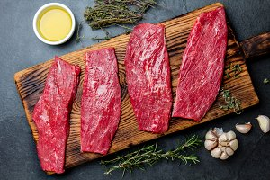 Fresh raw meat beef steaks. Beef tenderloin on wooden board, spices, herbs, oil on slate gray background. Food cooking background concept