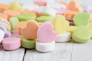 Closeup Candy Hearts on Wood Table