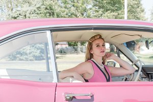 Sexy female in vintage pink car