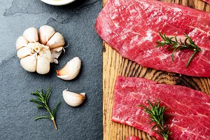 Fresh raw meat beef steaks. Beef tenderloin on wooden board, spices, herbs, oil on slate gray background. Food background with copy space