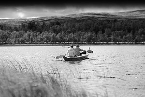 Black and white couple of tourists swimming in boat background