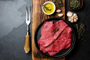 Fresh raw meat beef steaks. Beef tenderloin in cast iron pan on wooden board, spices, herbs, oil on slate gray background. Food background with copy space