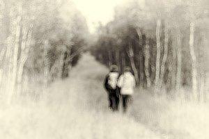 Couple walking through Norway woods bokeh backdrop