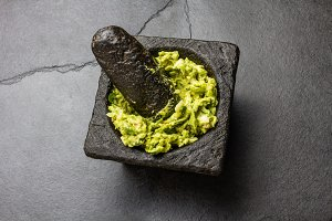 Traditional latin american mexican sauce guacamole in stone mortar, slate gray background