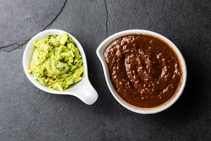 Traditional famous mexican sauces chocolate chili mole poblano, and avocado guacamole on slate gray background