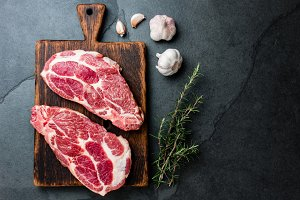 Raw pork cutlet chop for grill BBQ with herbs on wooden board, slate background, top view, copy spaces
