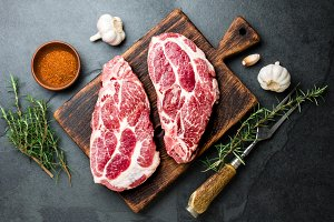Raw pork cutlet chop for grill BBQ with herbs on wooden board, slate background, top view