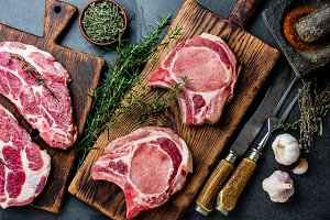 Raw pork cutlet chop for fry on grill and pan with herbs, garlic on wooden boards, slate gray background
