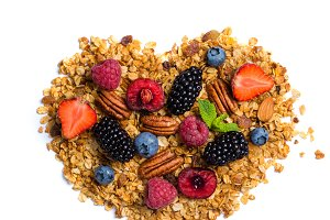 Healthy diet concept - heart shaped granola with nuts and berries