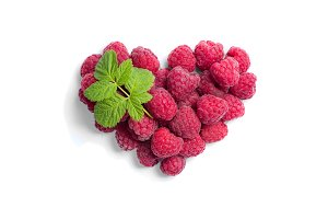 Heart shaped raspberries on white background