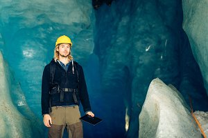 Scientist At An Expedition Site Examining A Glacier