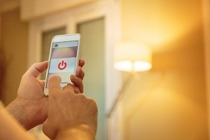 Smart Home: Man Controlling Lights With App On His Phone