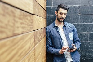 Attractive bearded young man with his smartphone