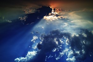 Horizontal dramatic sunset beams in cloudscape background
