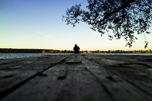 Lone fisherman sunset pier