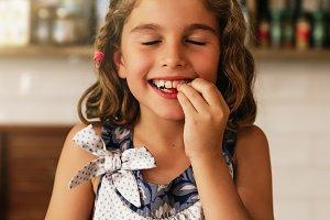 Little happy girl eating chocolate.