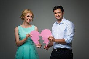 Beautiful couple holding pink broken heart