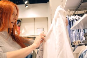 Red hair woman is choosing a dress in women's clothing store