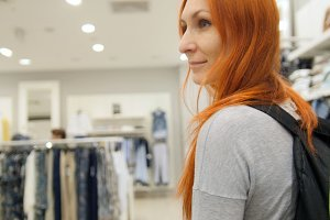 A red hair woman walking among dresses in clothes store