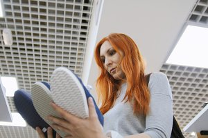 Attractive red haired woman chooses a sneakers in shoes store - shopping concept