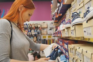 Shopping for women - young woman chooses a shoes in mall