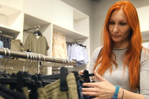 Yong positive woman is choosing a dress in women's clothing store