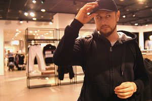Young man is choosing cap in mall or clothing store - shopping, fashion, style