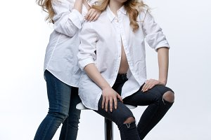 Two beautiful girls in white shirts and blue jeans