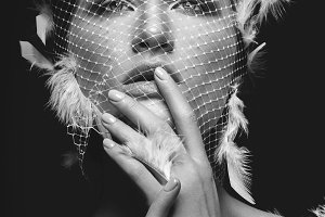 Beautiful girl in veil with feathers