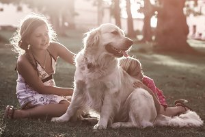 Two little girls with golden retriev