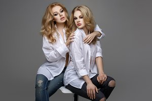 Two beautiful girls in white shirts and jeans