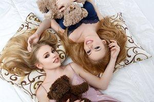 Two beautiful girls lying on pilloows