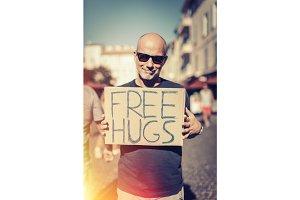 Man Holding Free Hugs Sign In European City