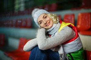 Beautiful girl in winter clothes sitting on rink tribune