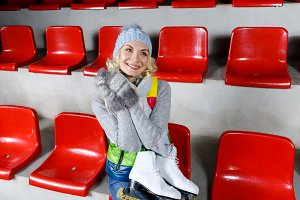 Beautiful girl in winter clothes with skates