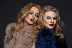Two beautiful girls in fashion fur coats