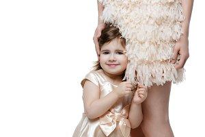 Adorable little girl in dress standing near mother