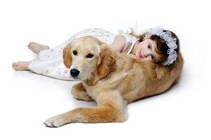 Little girl lying on golden retriever puppy