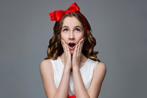 Surprised teen girl with red bow on head