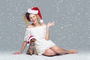 Beautiful girl with yorkie dog in santa cap