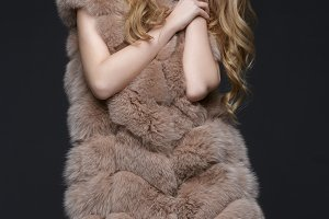 Beautiful girl with red lips in fur coat