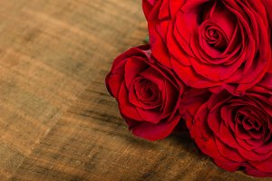 Three red roses on wooden table