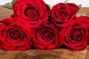 Five red roses on wooden table