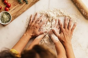 Close up of hands kneading flour.