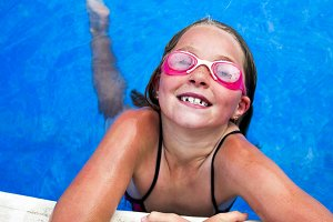Little girl in pool with goggles