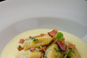 Spinach gnocchi with parmesan sauce topped with bacon