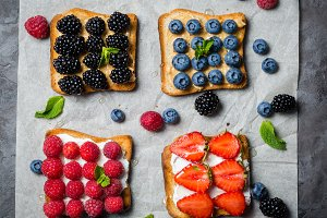 Selection of toasts with cheese peanut butter and berries